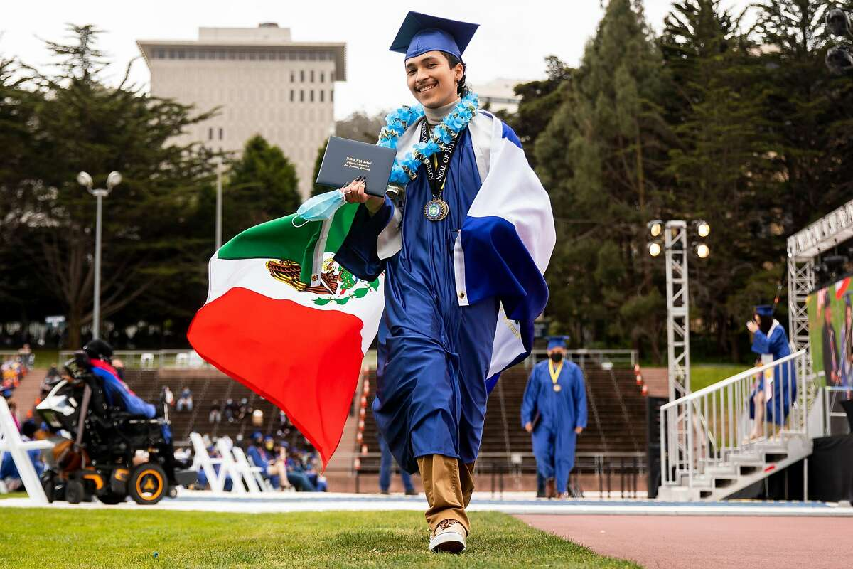 Rober Caceres drapes himself in a Mexican flag while walking off the stage with his diploma during Balboa High School's graduation ceremony at Kezar Stadium in San Francisco.