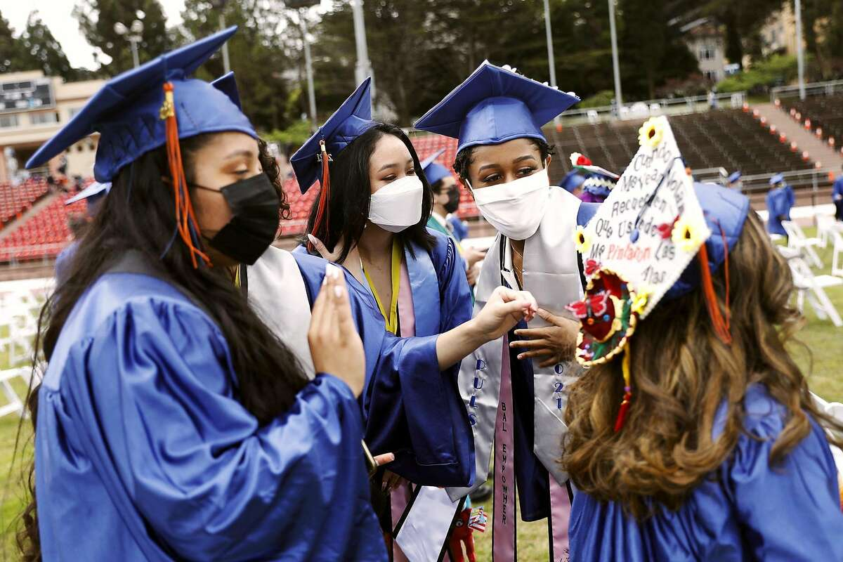Marvely Tomas (from left), Wendy Huang and Pierce Whitney admire Valeria Serrano's decorated cap before Balboa High School's graduation ceremony at Kezar Stadium in San Francisco.