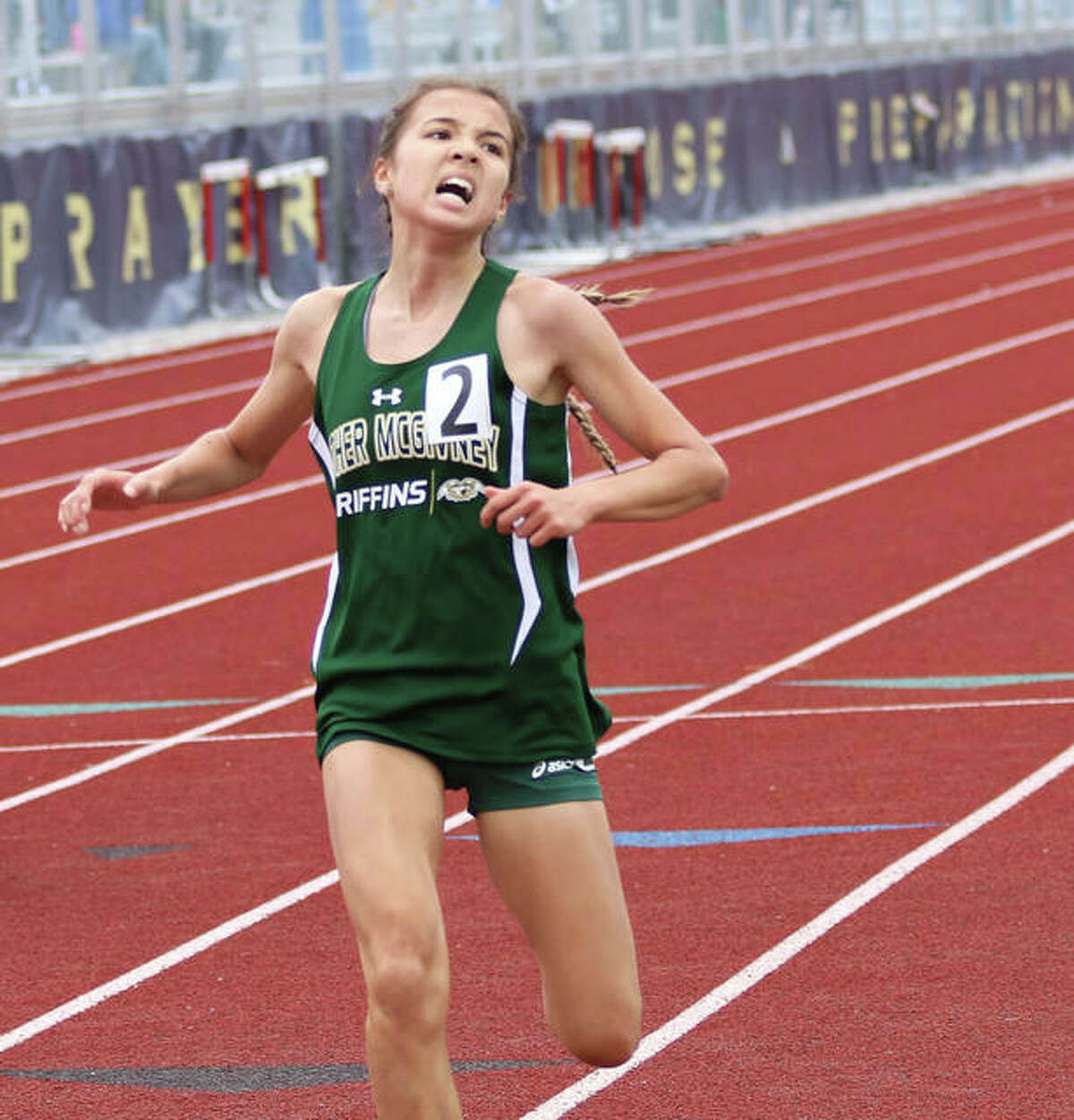 Father McGivney freshman Kaitlyn Hatley looks to the clock and her PR time crossing the finish line to win the 800 meters on Wednesday at the Althoff Class 1A Sectional in Belleville.