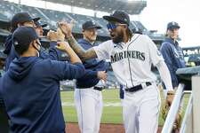 SEATTLE, WASHINGTON - JUNE 01: J.P. Crawford #3 of the Seattle Mariners high fives his teammates before the game against the Oakland Athletics at T-Mobile Park on June 01, 2021 in Seattle, Washington. (Photo by Steph Chambers/Getty Images)