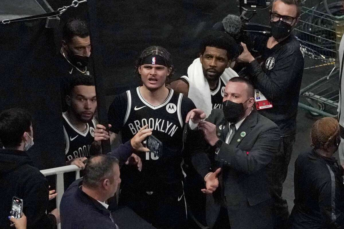 A security guard points as Brooklyn Nets' Kyrie Irving, right with towel, and teammates look up at a fan who reportedly threw a water bottle at him as he left the court after Game 4 during an NBA basketball first-round playoff series, Sunday, May 30, 2021, in Boston.