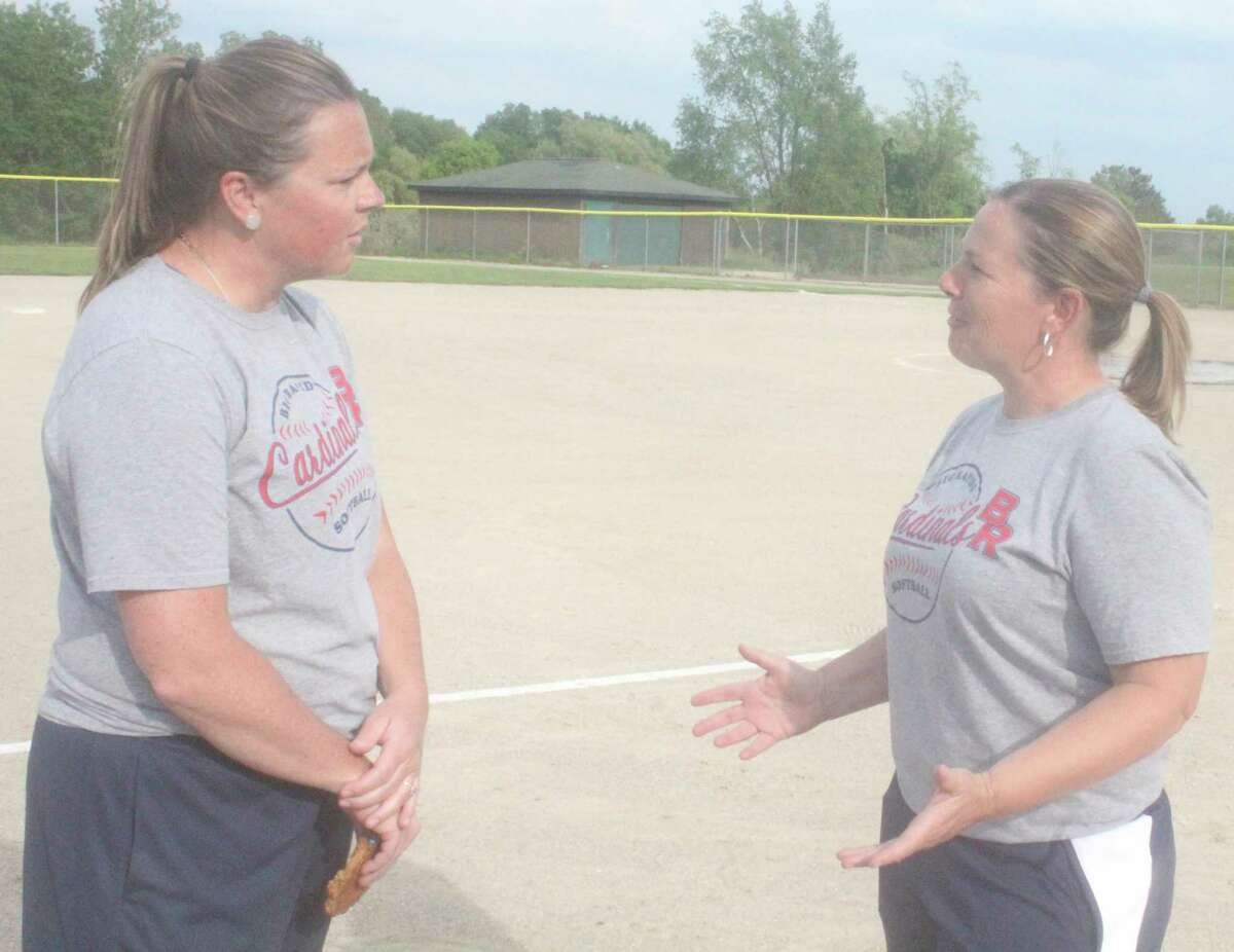 Big Rapids softball coach Dawn Thompson (right) discusses Saturday's districts with assistant coach Jenny Prince after Wednesday's 5-0 win over Kent City. (Pioneer photo/John Raffel)