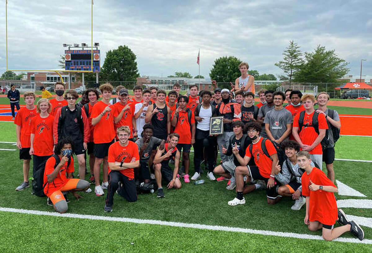 The Edwardsville Tigers pose with the Southwestern Conference championships for varsity and junior varsity after winning the titles in East St. Louis.