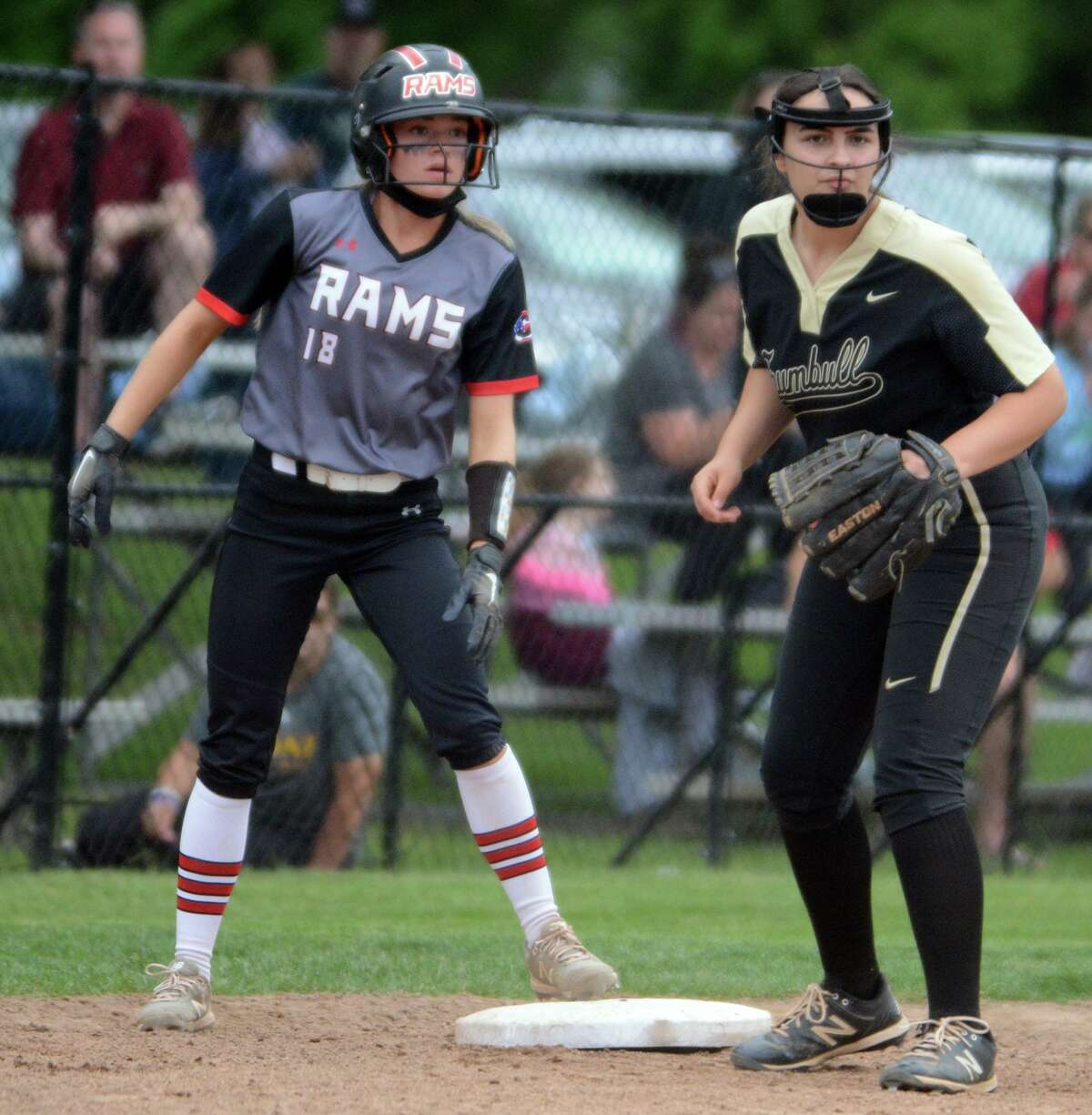 Cheshire's Grace Lurz (18) is held on at third base by Trumbull's Lianna Weaver during a second-round Class LL softball game on Wednesday in Cheshire.