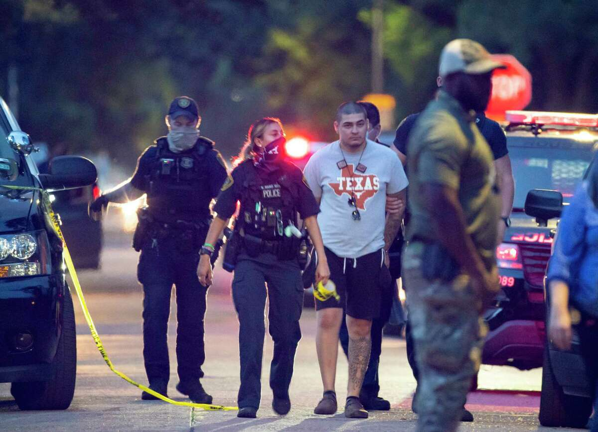 Police take a man into custody, taking him back into a home on McAvoy Street where Houston police say they are investigating a possible human smuggling operation, and then leading him back and putting him in a police SUV, Wednesday, June 2, 2021, in Houston. Law enforcement also transported several people separately in two vans.