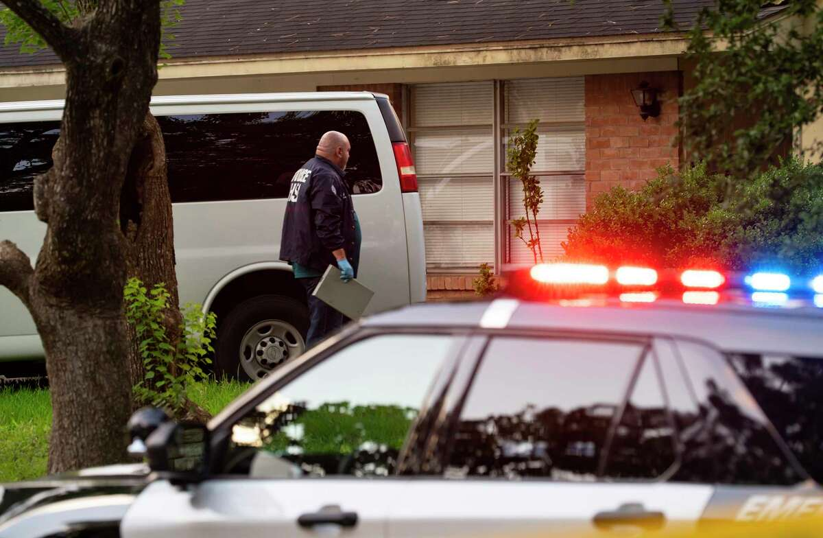 A police officer investigates a home on McAvoy Street where Houston police say they are investigating a possible human smuggling operation, Wednesday, June 2, 2021, in Houston.