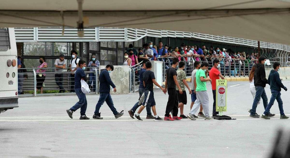 Varios inmigrantes son escoltados hacia un autobús en el Puente Internacional Hidalgo, el miércoles 2 de junio de 2021, en Hidalgo, Texas.