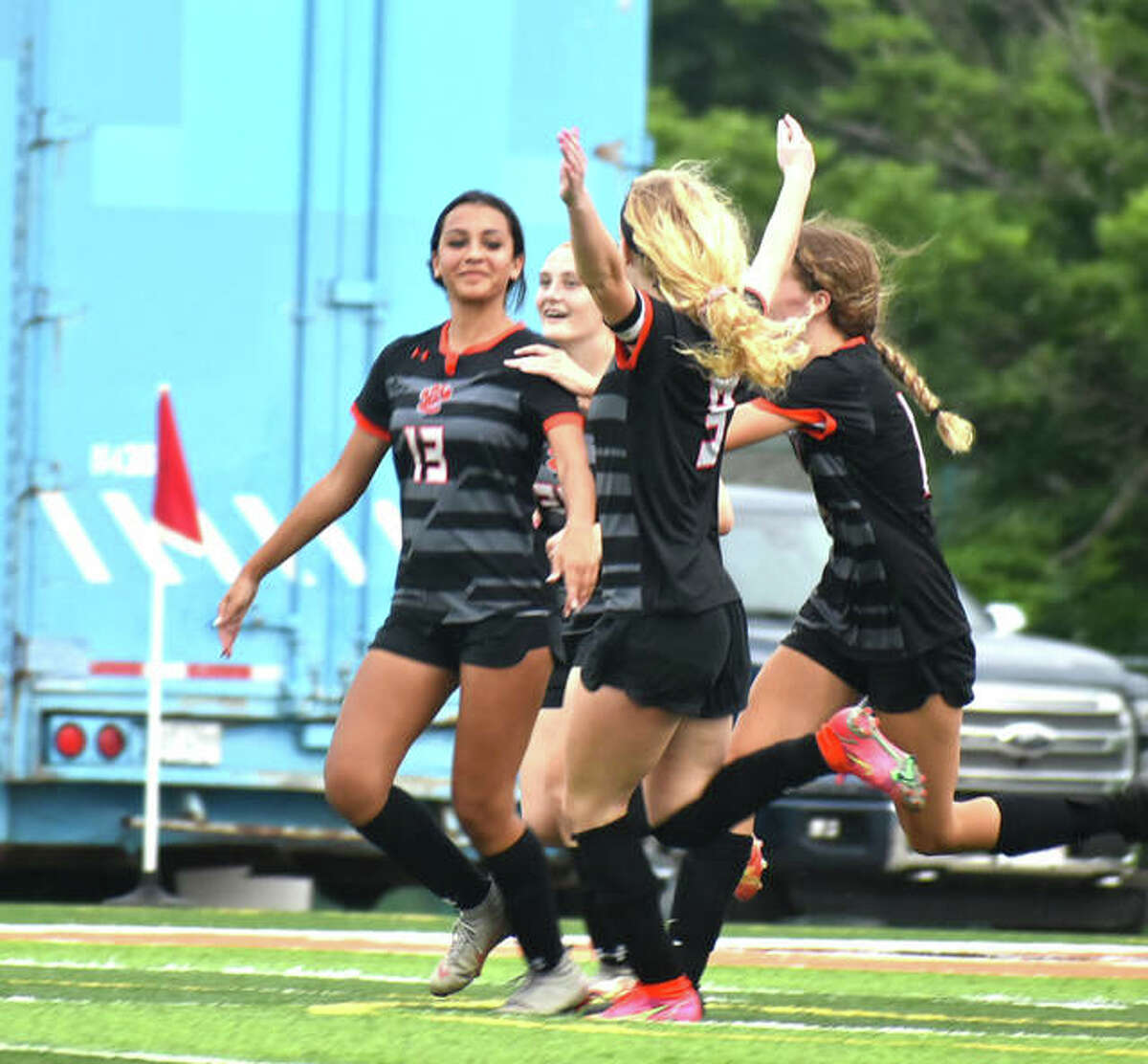 Edwardsville's Mariah Jackson, far left, is congratulated by teammates after her goal in the 44th minute against Quincy.