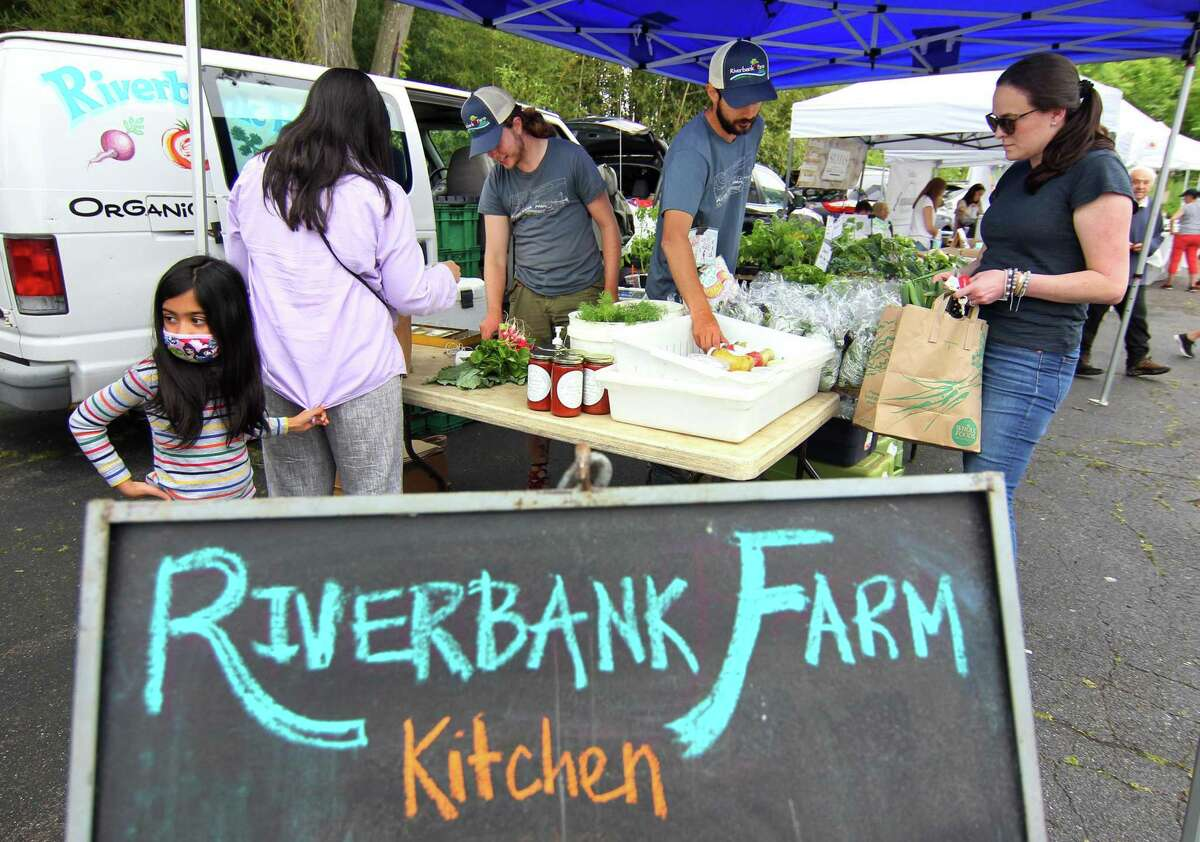 Rebecca Davis, at right, gets help from Brian Pacheco, with Riverbank Farms, during Opening Day of the Old Greenwich Farmer's Market at Living Hope Community Church in Greenwich, Conn., on Wednesday June 2, 2021. The Market is held rain or shine from 2:30 to 6 p.m. at Living Hope Community Church, 38 West End Avenue, Old Greenwich. Residents may also drop off their food scraps during market hours for Greenwich Composts.