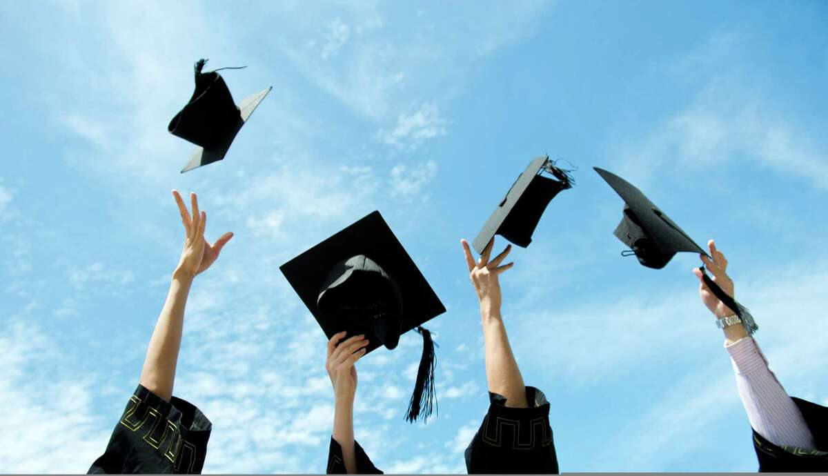 Graduates throw graduation hats in the air.
