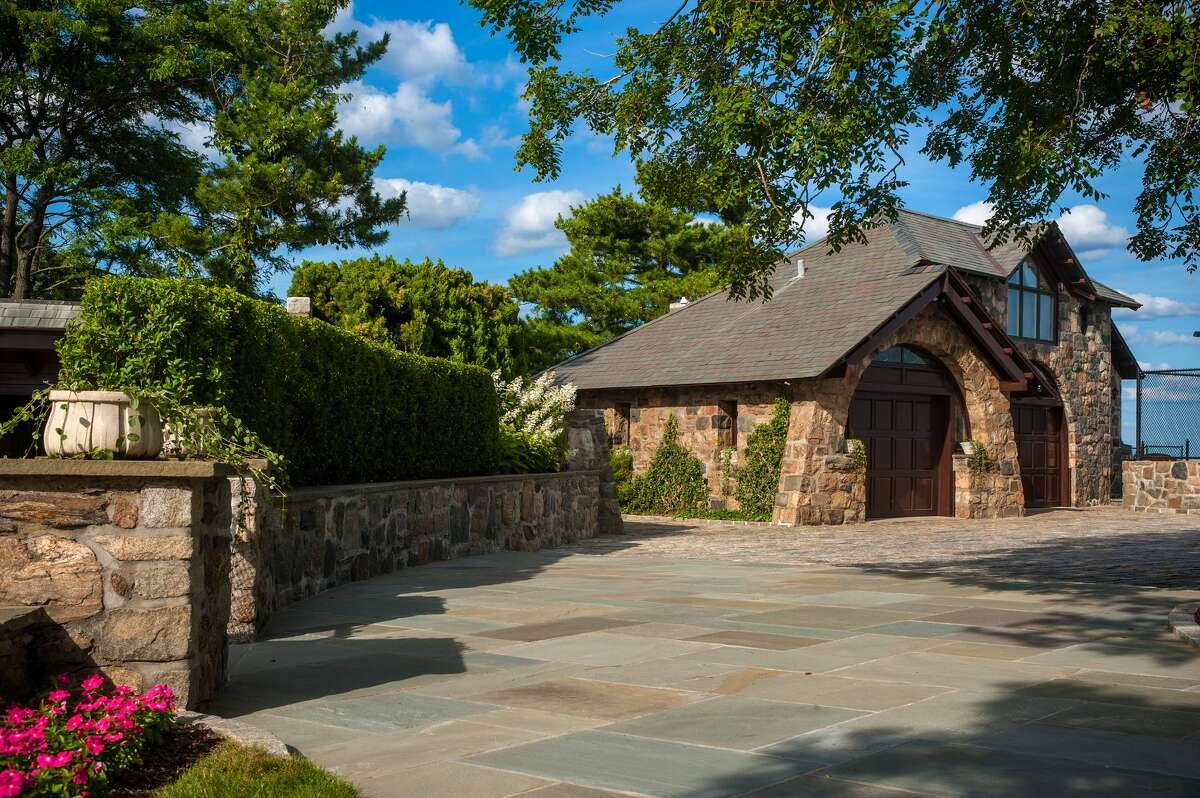 The property on which 123 Saddle Rock Road house sits also contains a stone guest cottage.