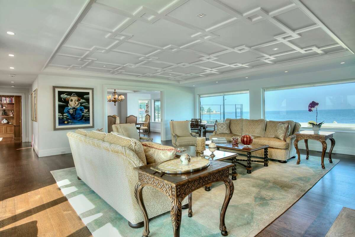 The living room in the 23 Saddle Rock Road home in Stamford, Conn. has glass walls that show a view of Long Island Sound.