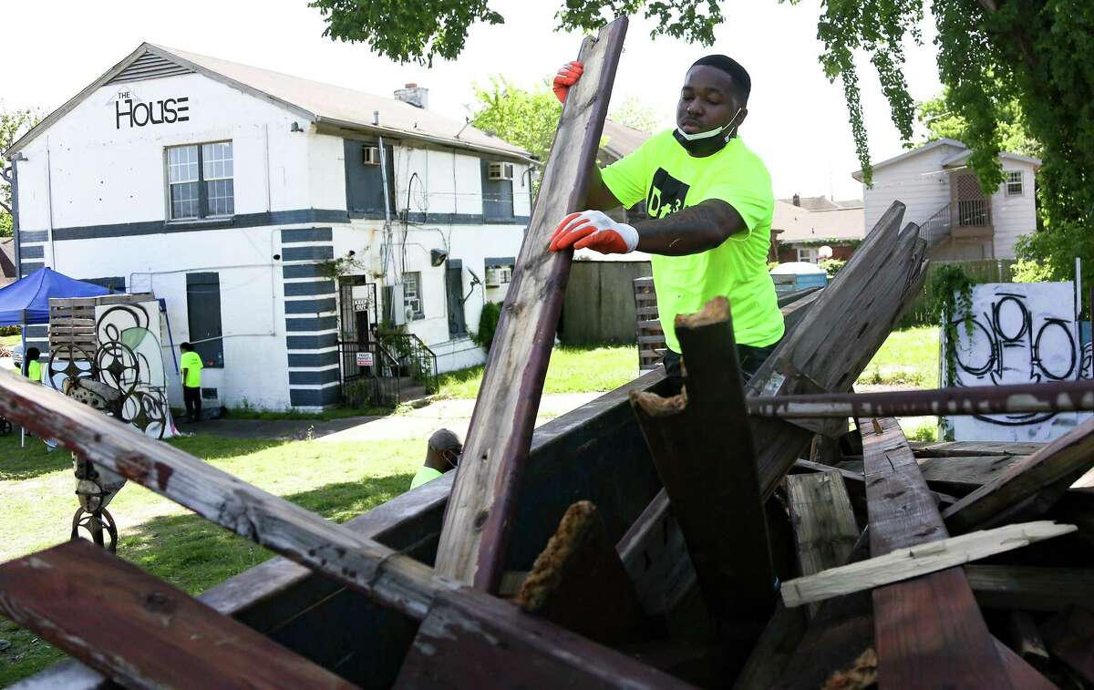 Volunteer Justin Taylor works on filing a trash container on property purchased by Third Ward Real Estate Council in Houston on Saturday, April 24, 2021.
