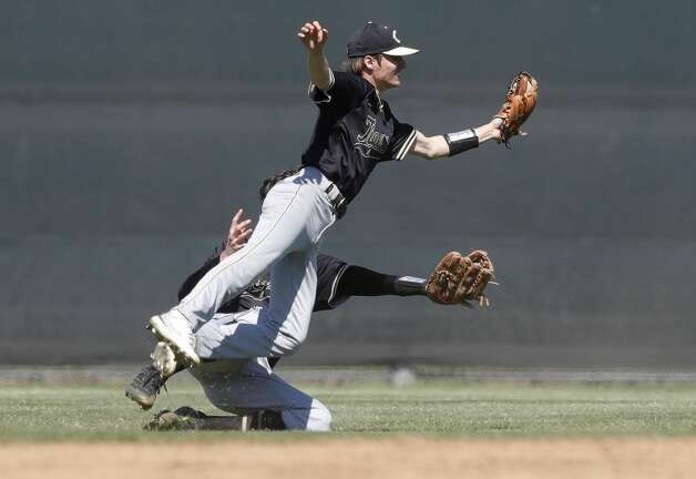 Conroe shortstop Garrett Cross (7) and center fielder Xander Nabors (17) collide while going for a fly ball from Harrison Helton #7 of College Park in the seventh inning of a District 13-6A high school baseball game at College Park High School, Friday, March 19, 2021, in The Woodlands. Cross hung onto the catch with Zack Cline at second base for the final out of the game for a 1-0 win over the Cavilers. Photo: Jason Fochtman/Staff Photographer