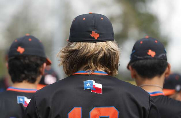 Baseball players are seen with custom Texas hats before a non-district high school baseball game at Grand Oaks High School, Saturday, March 13, 2021, in Spring. Photo: Jason Fochtman/Staff Photographer