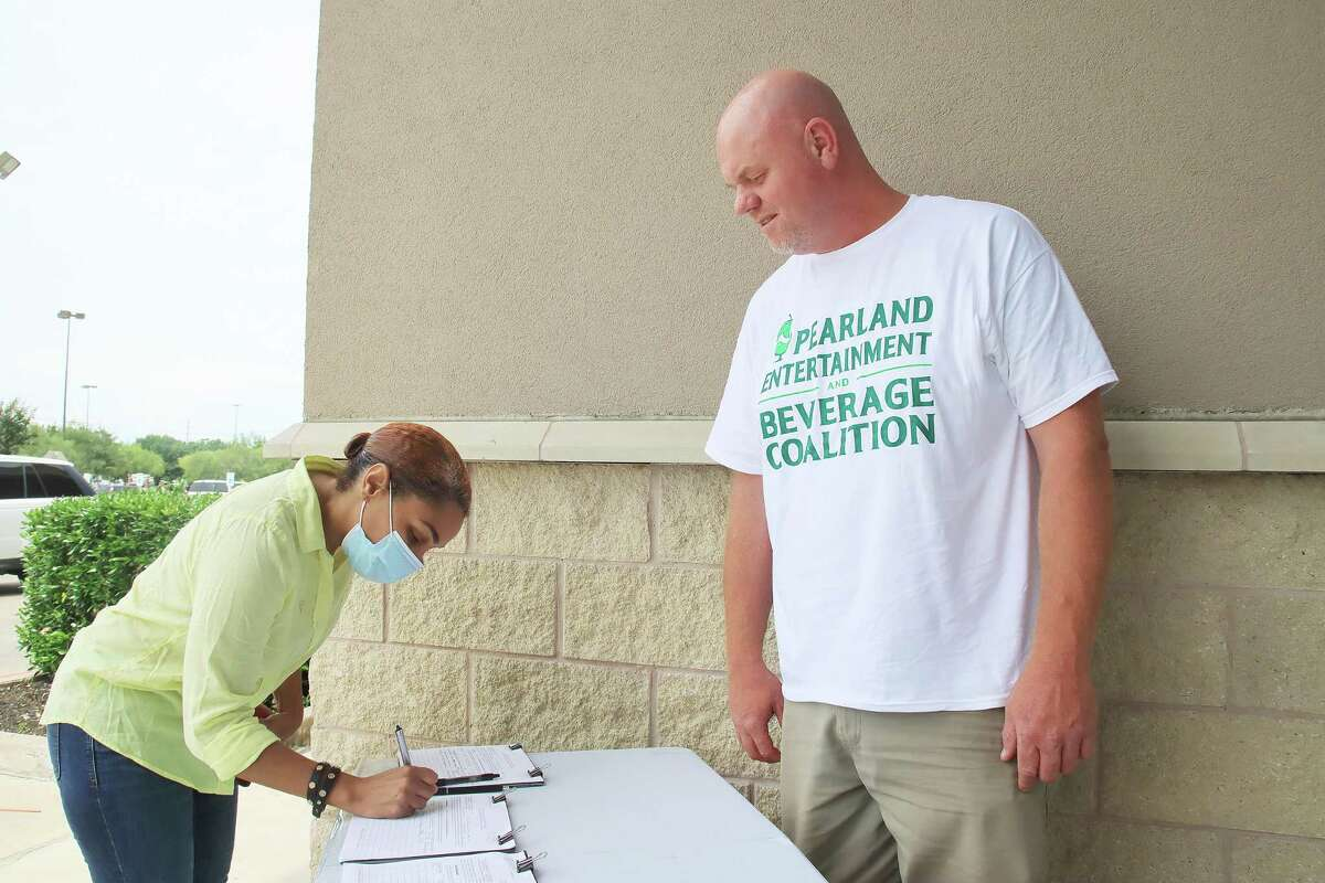 Robin Blunt signs a petition requesting that the city of Pearland place a measure on the November ballot to change the city's 51 percent rule regarding alcohol sales.