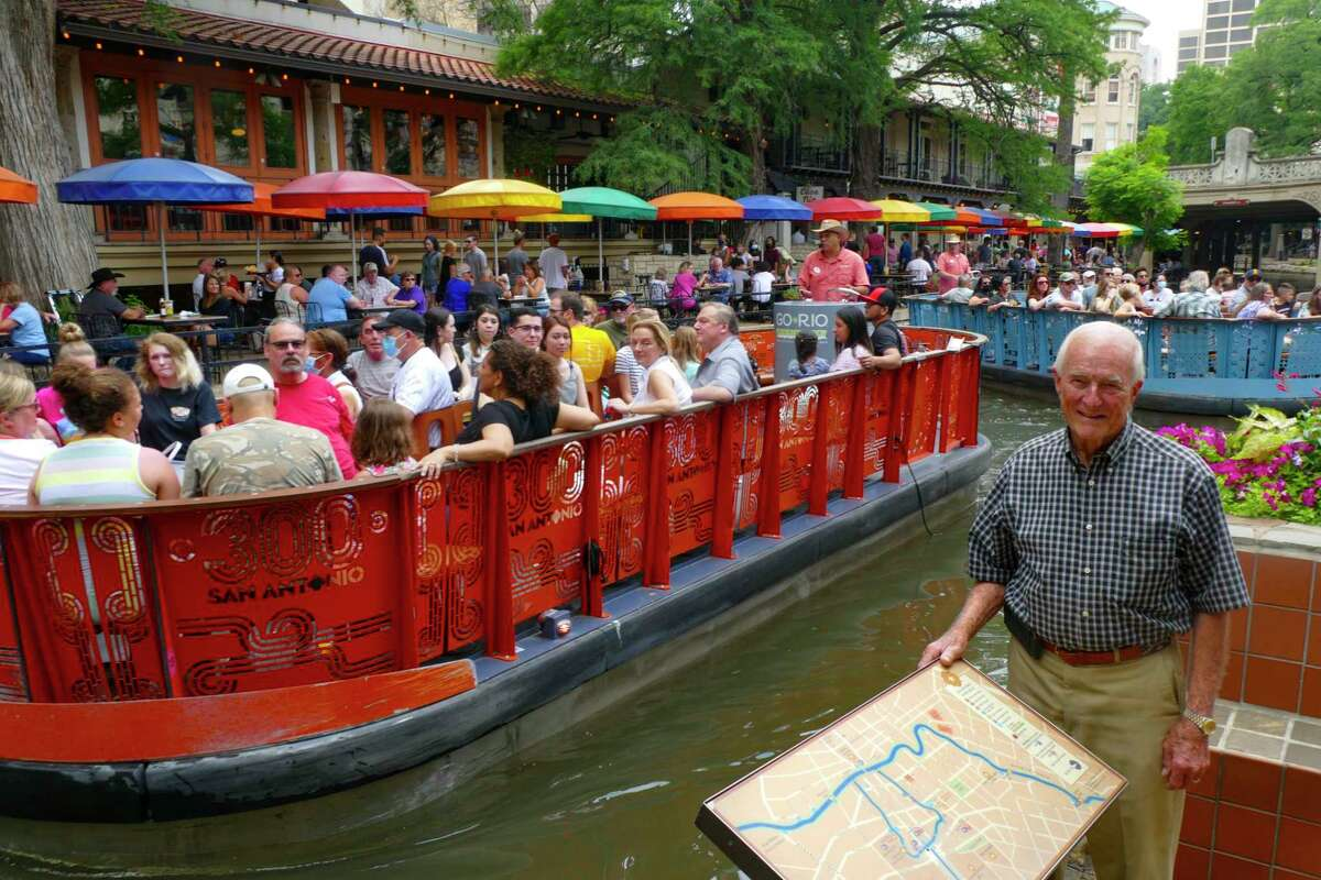 Bill Lyons, owner of Casa Rio restaurant on the River Walk, stands by the restaurant on the San Antonio River as a barge travels by on Friday, May 28, 2021. A dispute between restaurant owners and Go RIO, the operators of dinner barge tours, has prevented the dinner boats from returning.