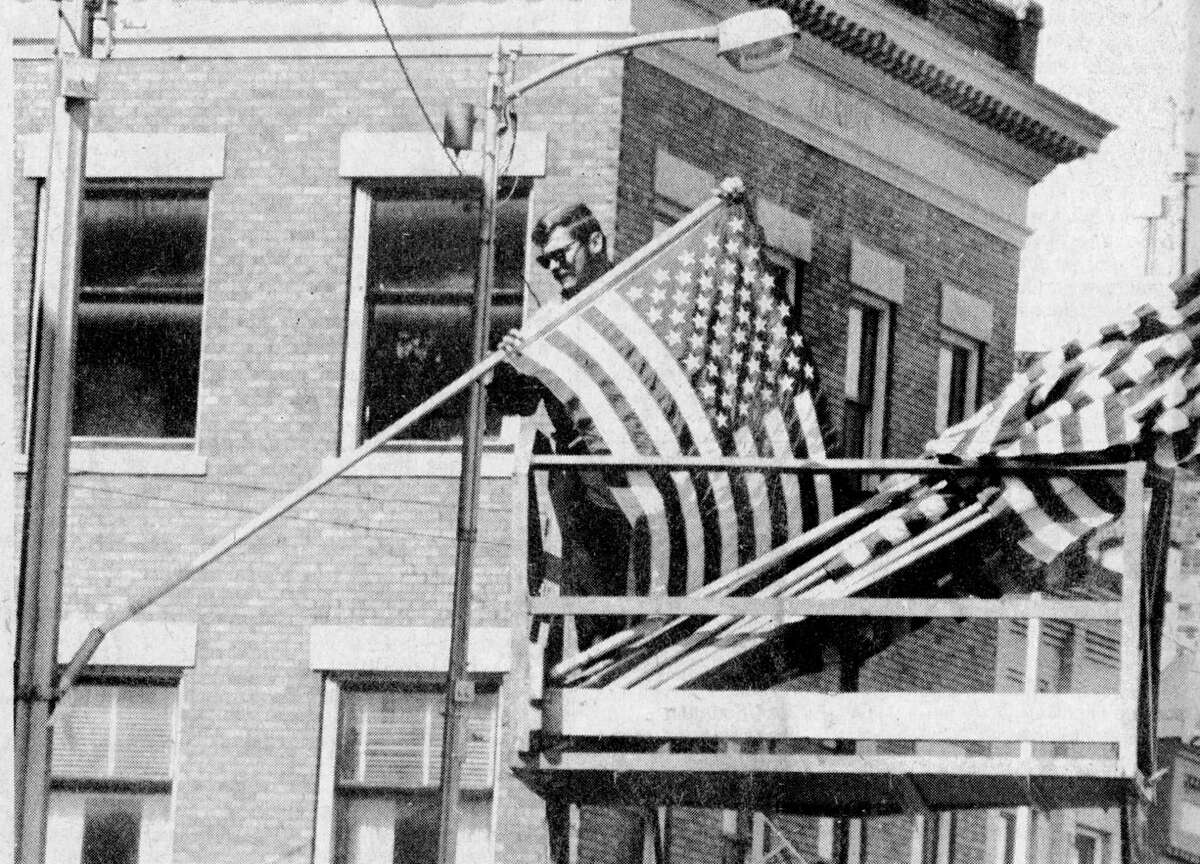 Jim Polisky, an employee of the City of Manistee, places American flags along the parade route in anticipation of the arrival of former Iranian hostage and former Manistee resident Robert Ode. Ode is in town to speak at Manistee High School graduation ceremonies tonight. The photo was published in the News Advocate on June 5, 1981. (Manistee County Historical Museum photo)