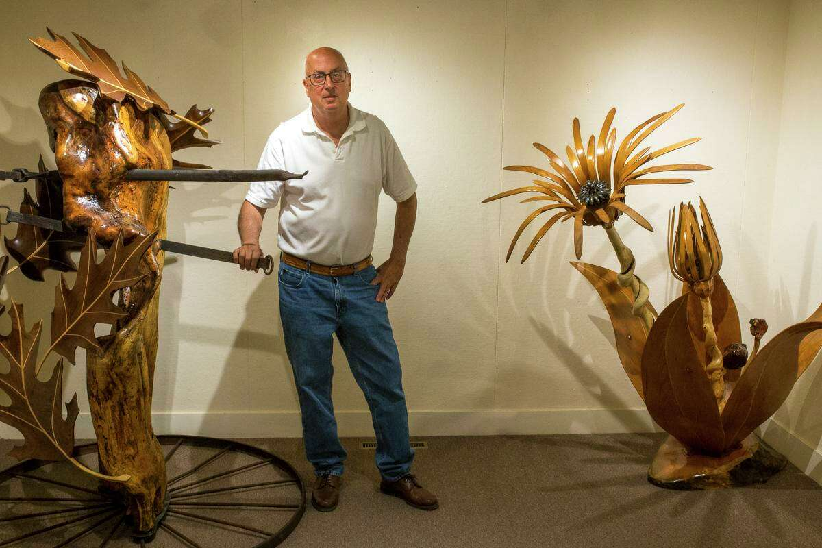Terrence Tougas with two of his wood pieces from his KAA Solo Show.