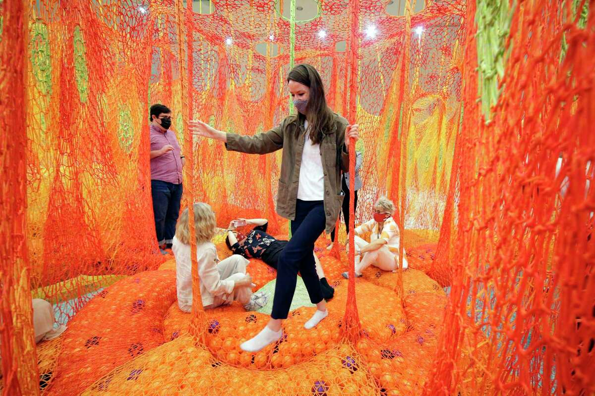 """Museum staff and visitors gather at the center of the labyrinth during a pre-opening look at the new interactive art installation by Brazilian artist Ernesto Neto, titled """"SunForceOceanLife"""", at the Museum of Fine Art Houston Saturday, May 29, 2021 in Houston, TX."""