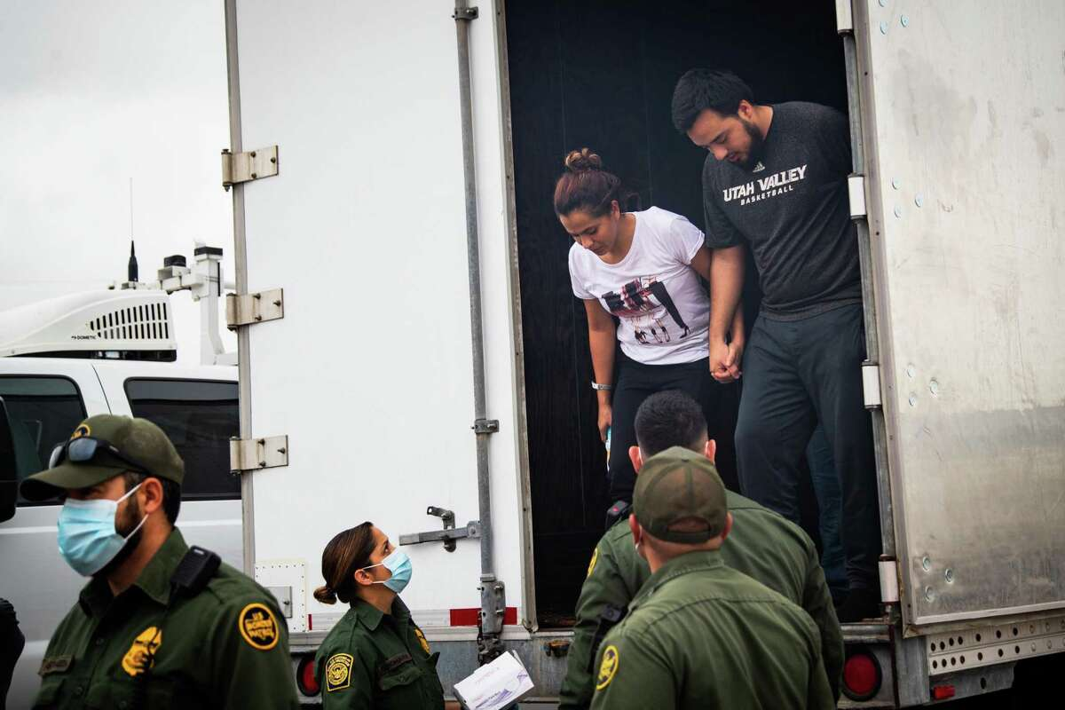 Two people holdings hands exit a cargo trailer as they are processed after being found with several dozen other people inside a trailer at a U.S. Customs and Border Protection inspection station at Interstate 35, are mobilized to be processed, Wednesday, May 26, 2021, in Laredo. The group are suspected of crossing the U.S./Mexico border unauthorized.