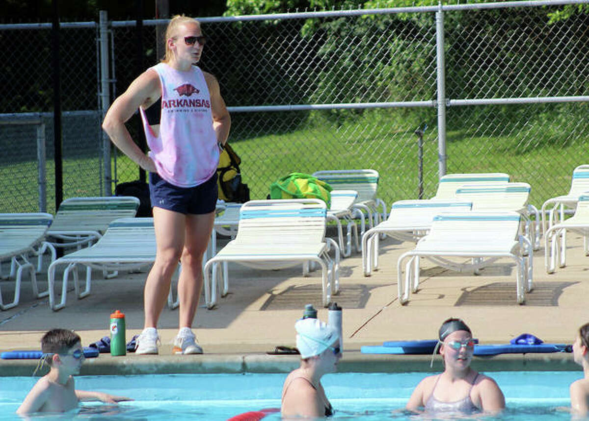 Summers Port head coach Maddie Monroe talks to some of her swimmers during the team's first practice of the season Thursday morning at the Godfrey pool. The Sharks will open their season June 10 at home against Montclaire.