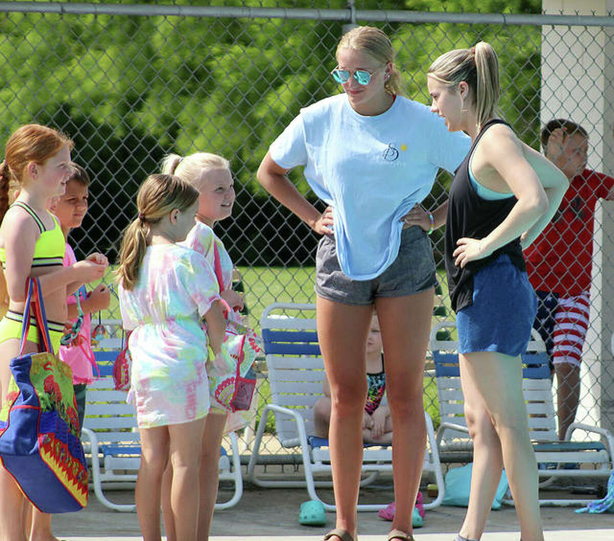 Summers Port assistant coaches Anna Moehn, left, and Ginny Schranck greet some of the younger swimmers at the first practice of the season.