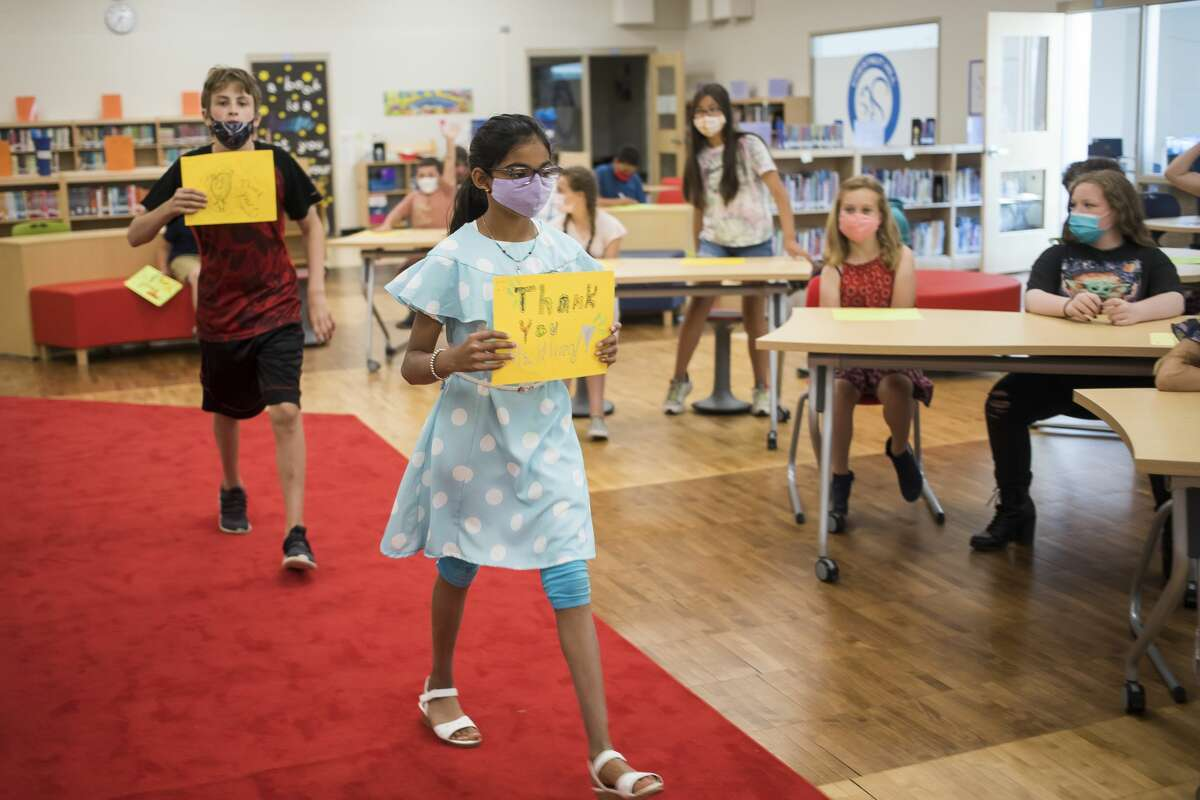 Archa Nair, center, and Michael York, left, both fifth graders at Chestnut Hill Elementary, walk down the