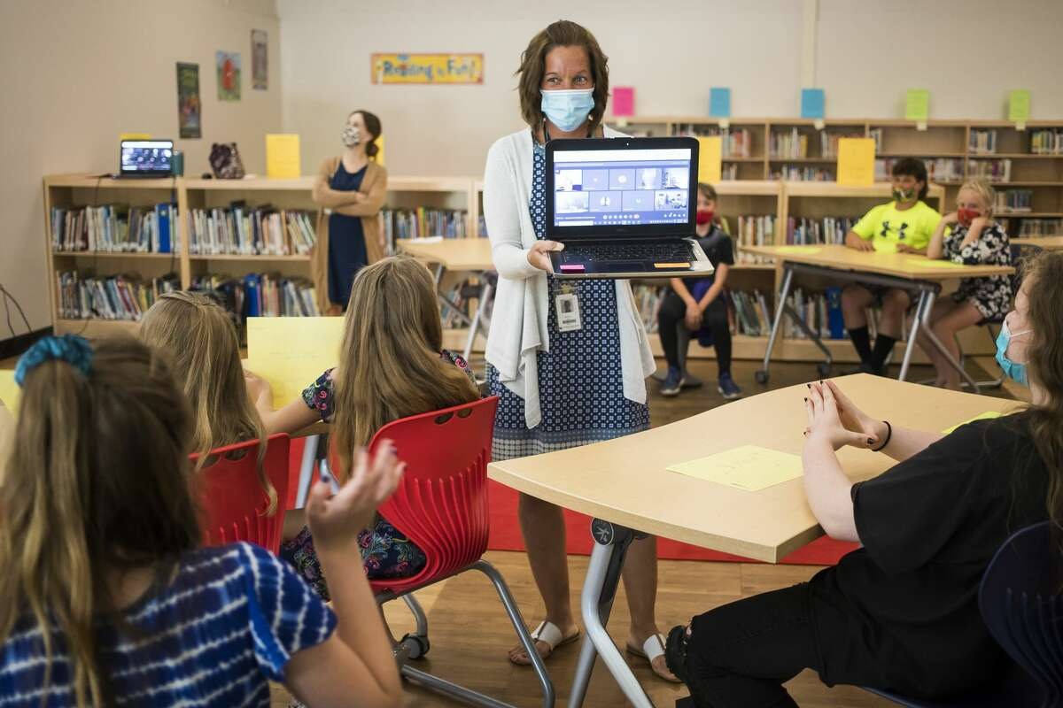 Stephanie Parker allows her fifth grade students to wave to their parents who joined virtually to watch them present their final PYP exhibition video projects Thursday, June 3, 2021 at Chestnut Hill Elementary in Midland. The students each picked an issue that they care about, researched the topic and even took action towards a solution. (Katy Kildee/kkildee@mdn.net)