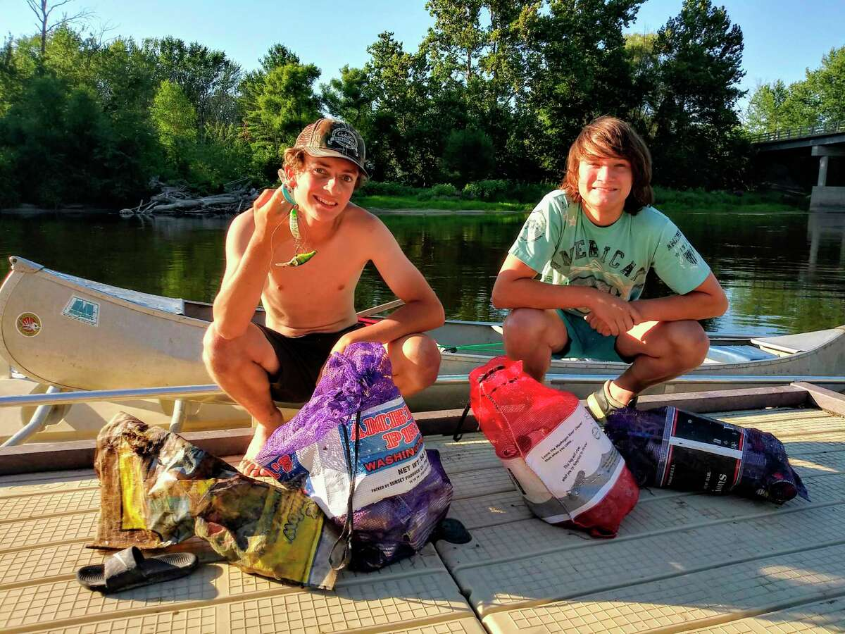 Volunteers collect bags of trash along the Muskegon River during the Muskegon River Trash Bash. (Photo courtesy of Lindsay Isenhart)