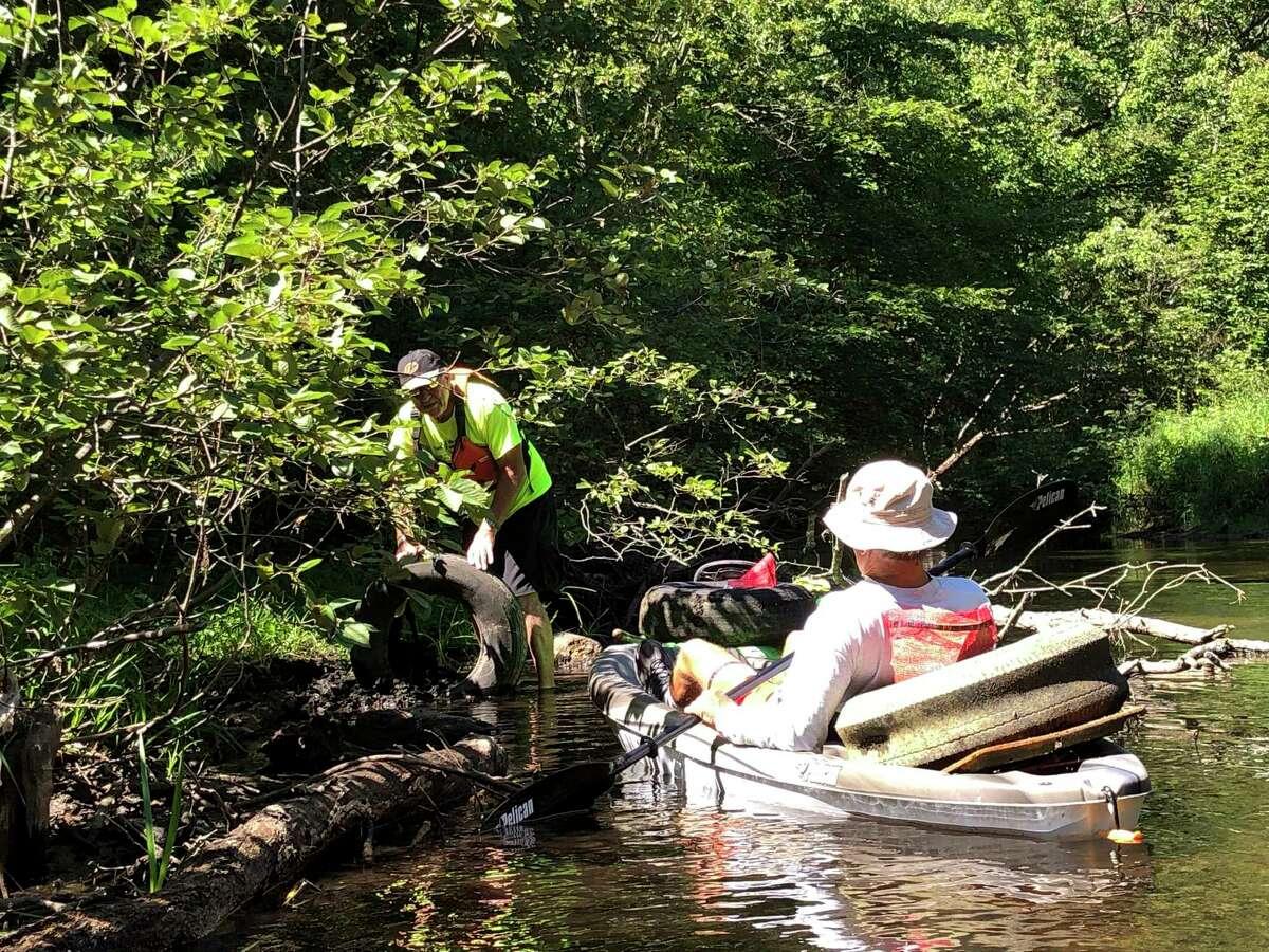 Volunteers pick up trash while boating along the Muskegon River during the Muskegon River Trash Bash. (Photo courtesy of Joseph Lisuzzo)