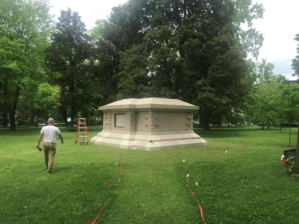 """A """"Gilded Age"""" employee strolls in Washington Park in Troy, N.Y., toward the replica of the base that supported the Statue of Liberty's hand holding the torch from 1876 to 1882."""