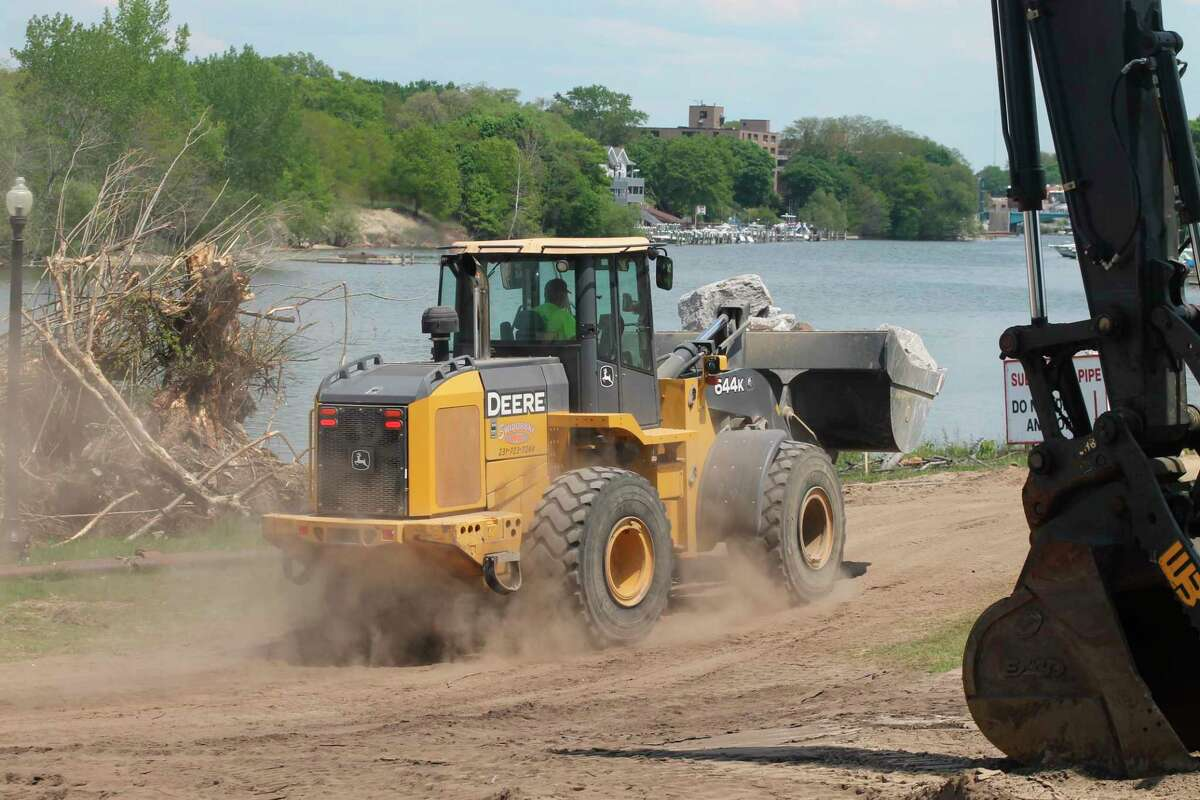 A loadercarries a load of rock Wednesday and workers continued repairs on the Manistee Riverwalk. (Kyle Kotecki/News Advocate)