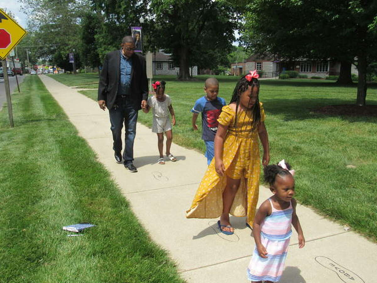 Alton Mayor David Goins takes his grandchildren on a poetry walk Thursday near the Robert Wadlow statue.
