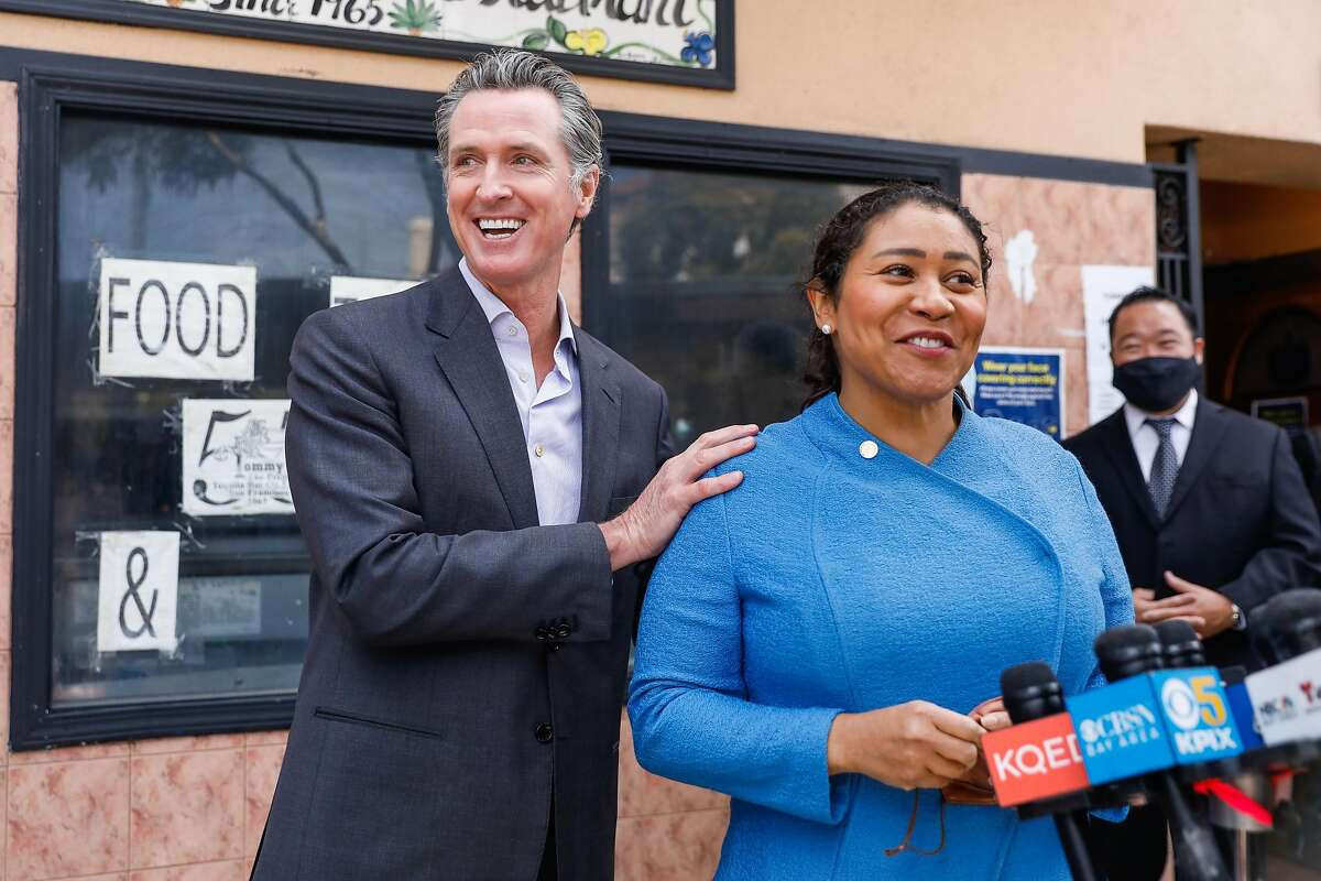 Governor Gavin Newsom jokes around with Mayor London Breed as she speaks during a press conference to discuss the measures the state is taking to support restaurants and bars ahead of California's June 15 reopening on Thursday, June 3, 2021 in San Francisco, California.