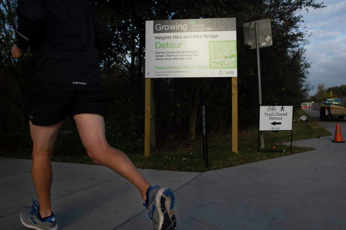 Signs notifying people to make a detour from the Heights Hike and Bike Trail to White Oak Bayou Trail are placed at the junction before the M-K-T Bridge on Dec. 16, 2020, at in Houston. The bridge, which carries the Heights Hike and Bike Trail across White Oak Bayou, has been closed since August because of a brush fire.