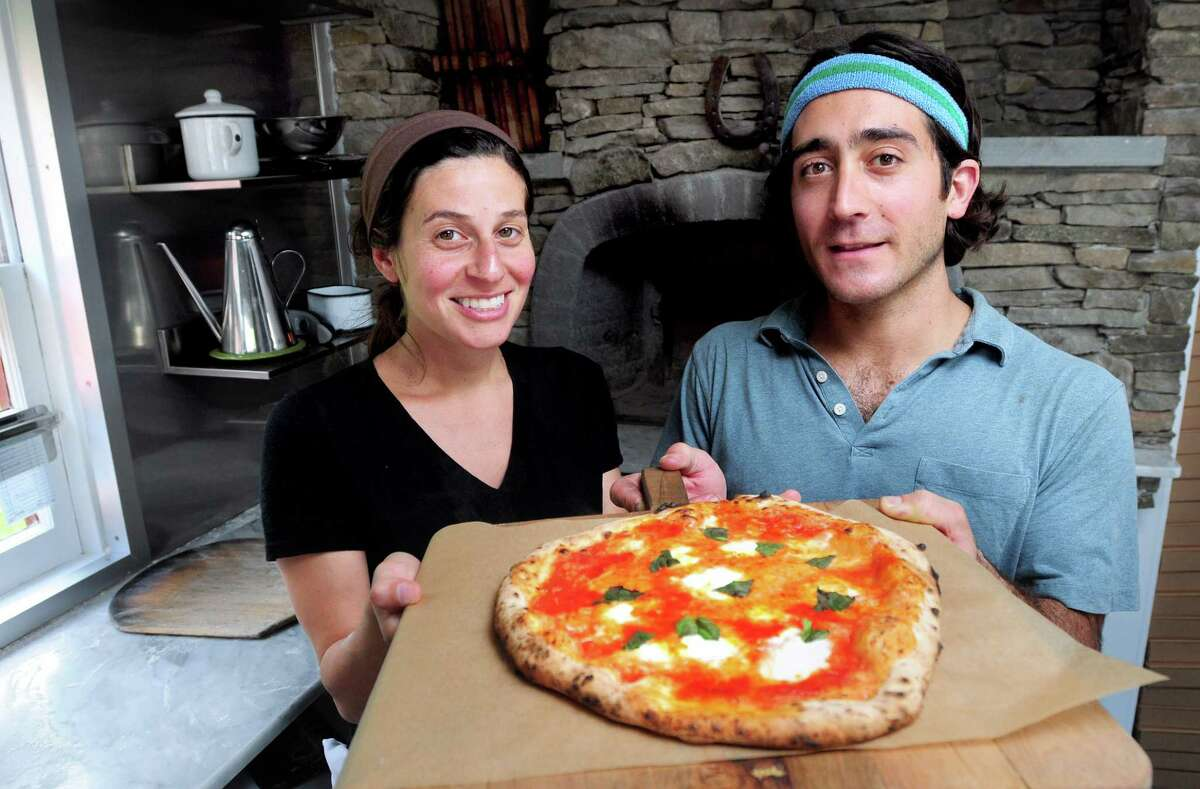 Melissa Pellegrino (left) is photographed with her husband, Matthew Scialabba, holding a Bufalina pizza with Buffalo mozzarella and basil at their restaurant, Bufalina Wood Fired Pizza in Guilford.