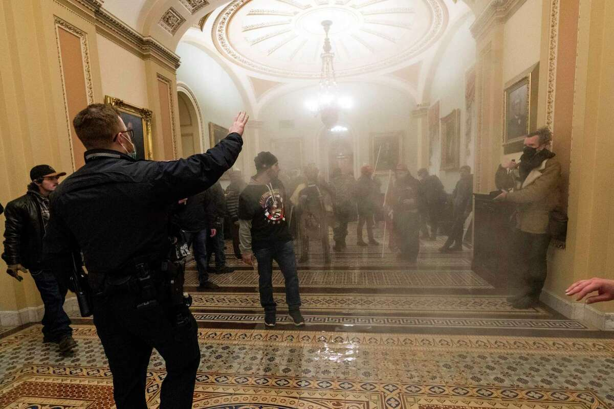 FILE - In this Jan. 6, 2021, file photo, smoke fills the walkway outside the Senate Chamber as rioters are confronted by U.S. Capitol Police officers inside the Capitol in Washington. Outside pressures and internal strife are roiling two far-right extremist groups after members were charged in the attack on the U.S. Capitol. Former President Donald Trump's lies about a stolen 2020 election united an array of right-wing supporters, conspiracy theorists and militants on Jan. 6. (AP Photo/Manuel Balce Ceneta, File)