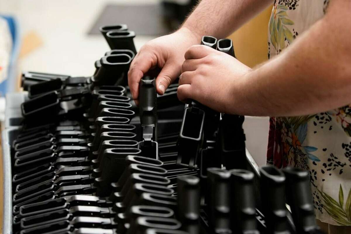 A worker places pistol grips for an AR-15 style rifle on a cart at Davidson Defense in Orem, Utah on February 4, 2021. - Gun merchants sold more than 2 million firearms in January, a 75% increase over the estimated 1.2 million guns sold in January 2020, according to the National Shooting Sports Federation, a firearms industry trade group. The FBI said it conducted a record 4.3 million background checks in January. If that pace continues, the bureau will complete more than 50 million gun-related background checks by the end of the year, shattering the current record set in 2020, according to a new report from Bespoke Investment Group.