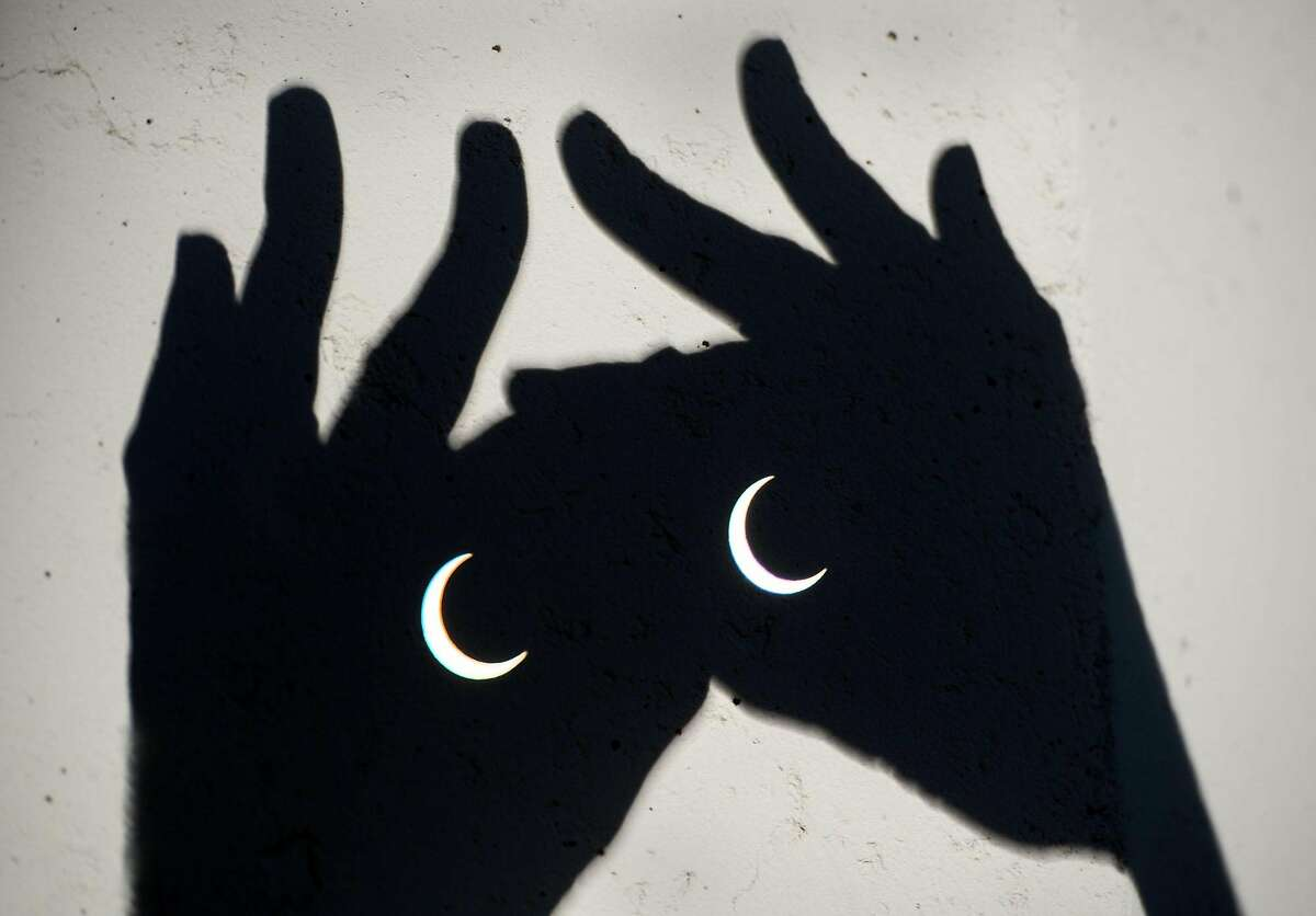 The annular eclipse is visible through binoculars in Sacramento, Calif., Sunday, May 20, 2012. The annular eclipse, in which the moon passes in front of the sun leaving only a golden ring around its edges, was visible to wide areas across China, Japan and elsewhere in the region before moving across the Pacific to be seen in parts of the western United States. (AP Photo/The Sacramento Bee, Randy Pench) MAGS OUT; TV OUT; MANDATORY CREDIT