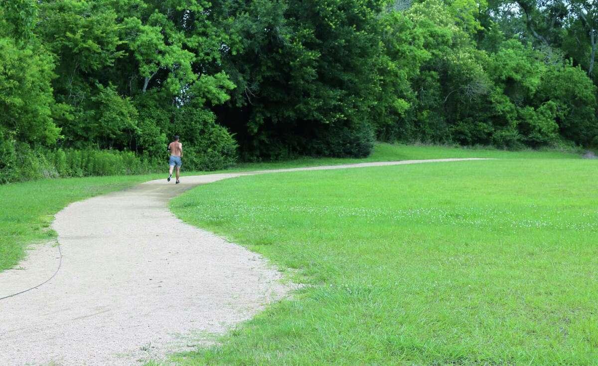 A lone runner navigates the curves of the path at the Armand Bayou Hike & Bike trail.