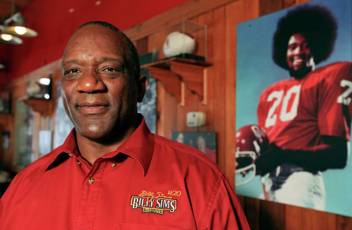"""1978 Heisman Trophy winner Billy Sims of Oklahoma, shown in a 2013 photo at his namesake barbecue restaurant in Tulsa, says college football has evolved into """"a big-time business."""""""