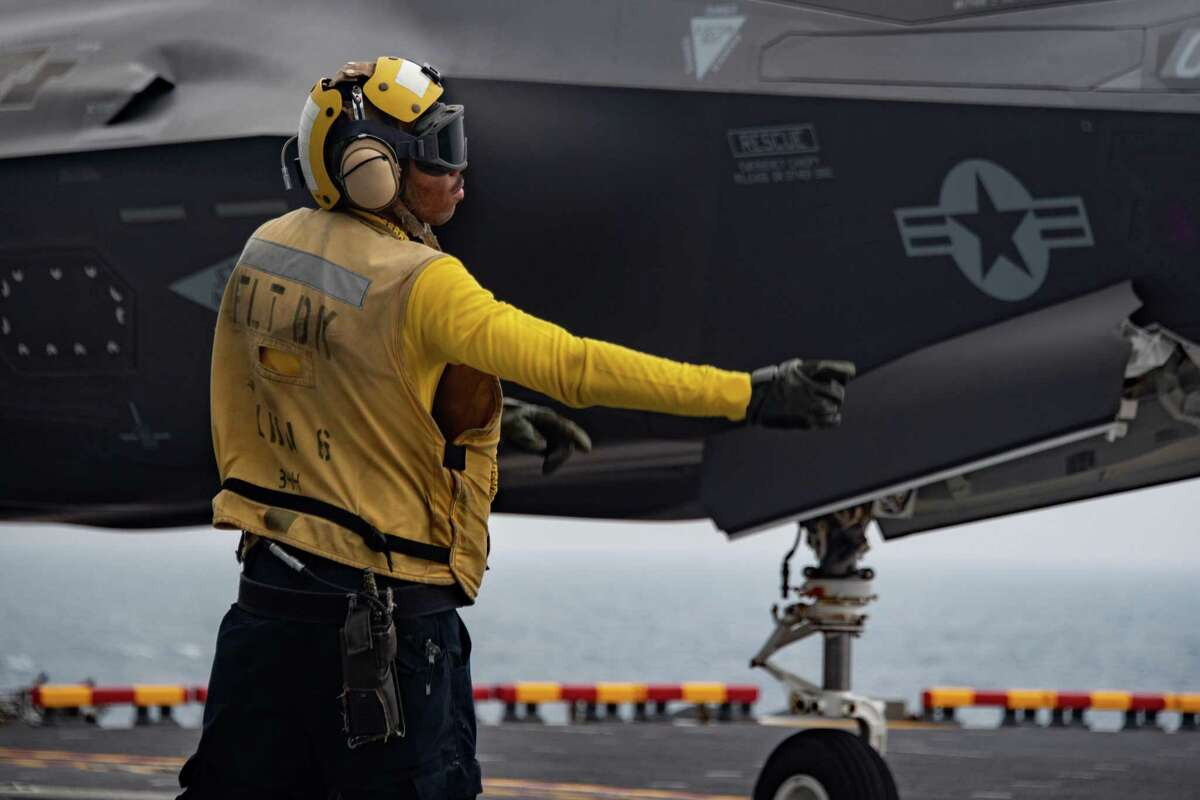 Aviation Boatswain's Mate (Handling) Airman Micah Callwood, from New Haven, assigned to the forward-deployed amphibious assault ship USS America (LHA 6), signals an F-35B Lightning from the 31st Marine Expeditionary Unit (MEU). America, lead ship of Amphibious Ready Group, along with the 31st MEU, is operating in the U.S. 7th Fleet area of responsibility to enhance interoperability with allies and partners and serve as a ready response force to defend peace and stability in the Indo-Pacific region.