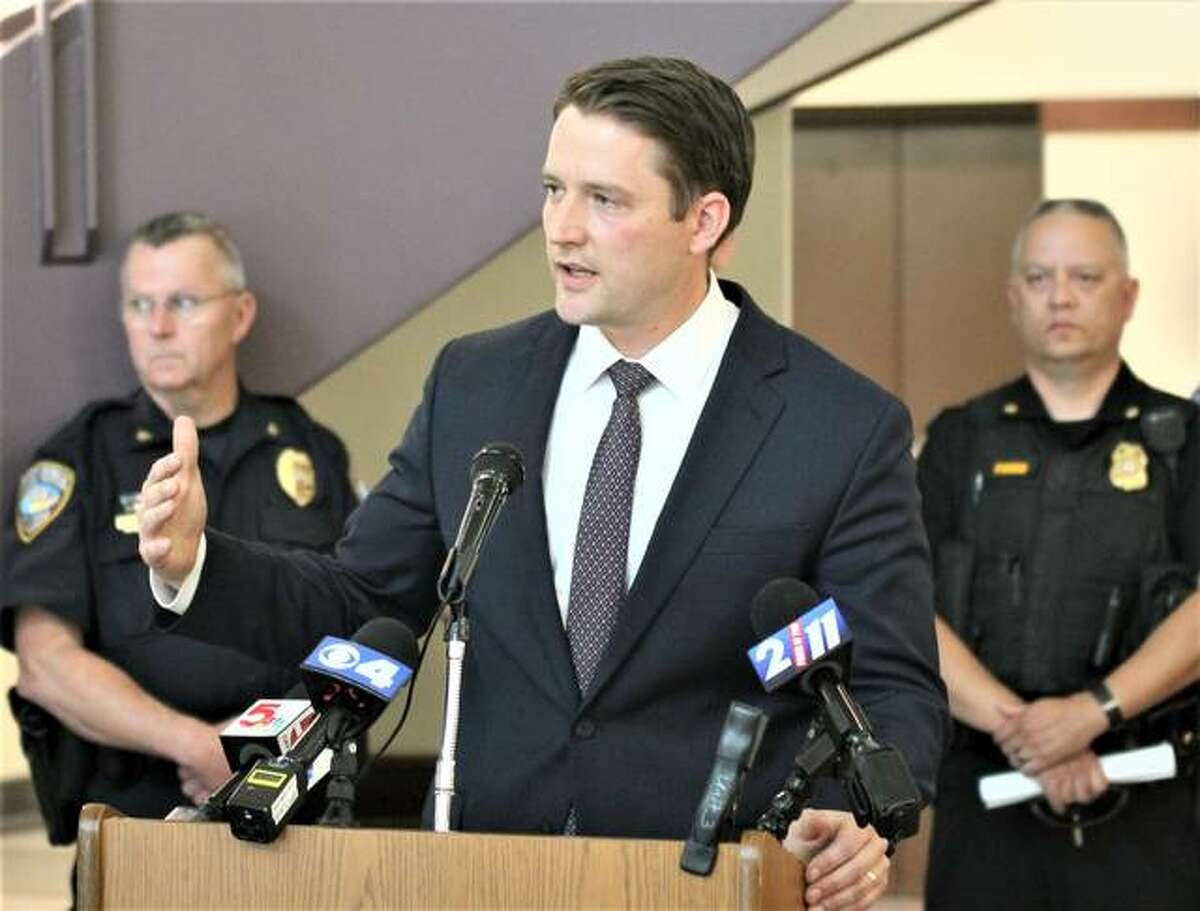 Flanked by local law enforcement officials, Madison County State's Attorney Tom Haine gives an update on the