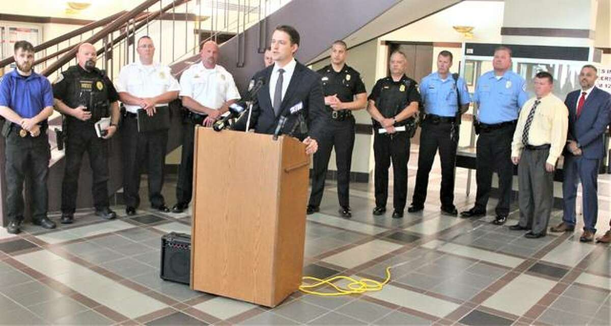 """Flanked by local law enforcement officials, Madison County State's Attorney Tom Haine gives an update on the """"Cross-River Crime Task Force"""" Thursday at the Madison County Administration Building, in Edwardsville. The task force formed in April to deal with increasing crime and criminals coming to the state from Missouri."""