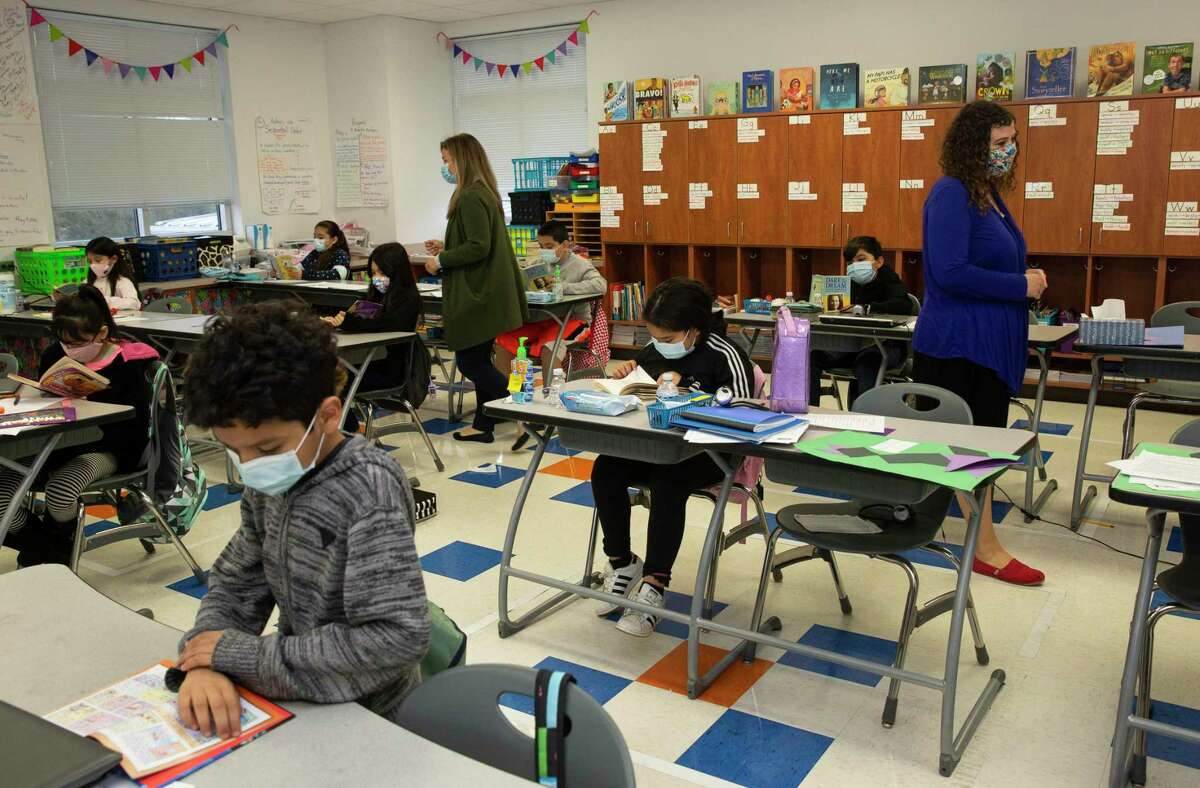 DeAnda Elementary School Principal Lauren Mailhiot, pictured at left in February, and fourth-grade teacher Hillary Smith work with an independent reading class at the Houston ISD campus.