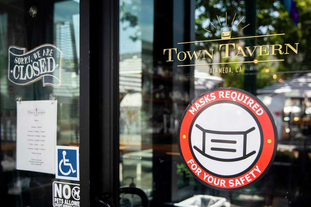 A sign reminds customers to mask up before entering Town Tavern along Park Street in Alameda, Calif. Friday, May 28, 2021.