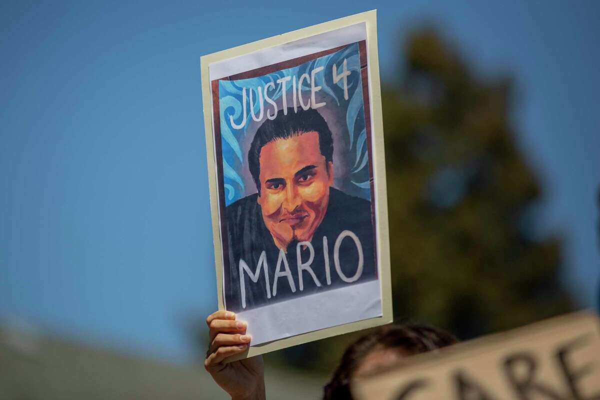 """A person holds up a """"Justice 4 Mario"""" sign while listening in to a news conference hosted by Mario Gonzalez's family and supporters outside the Alameda Police Department on Tuesday, April 27, 2021, in Alameda, Calif."""