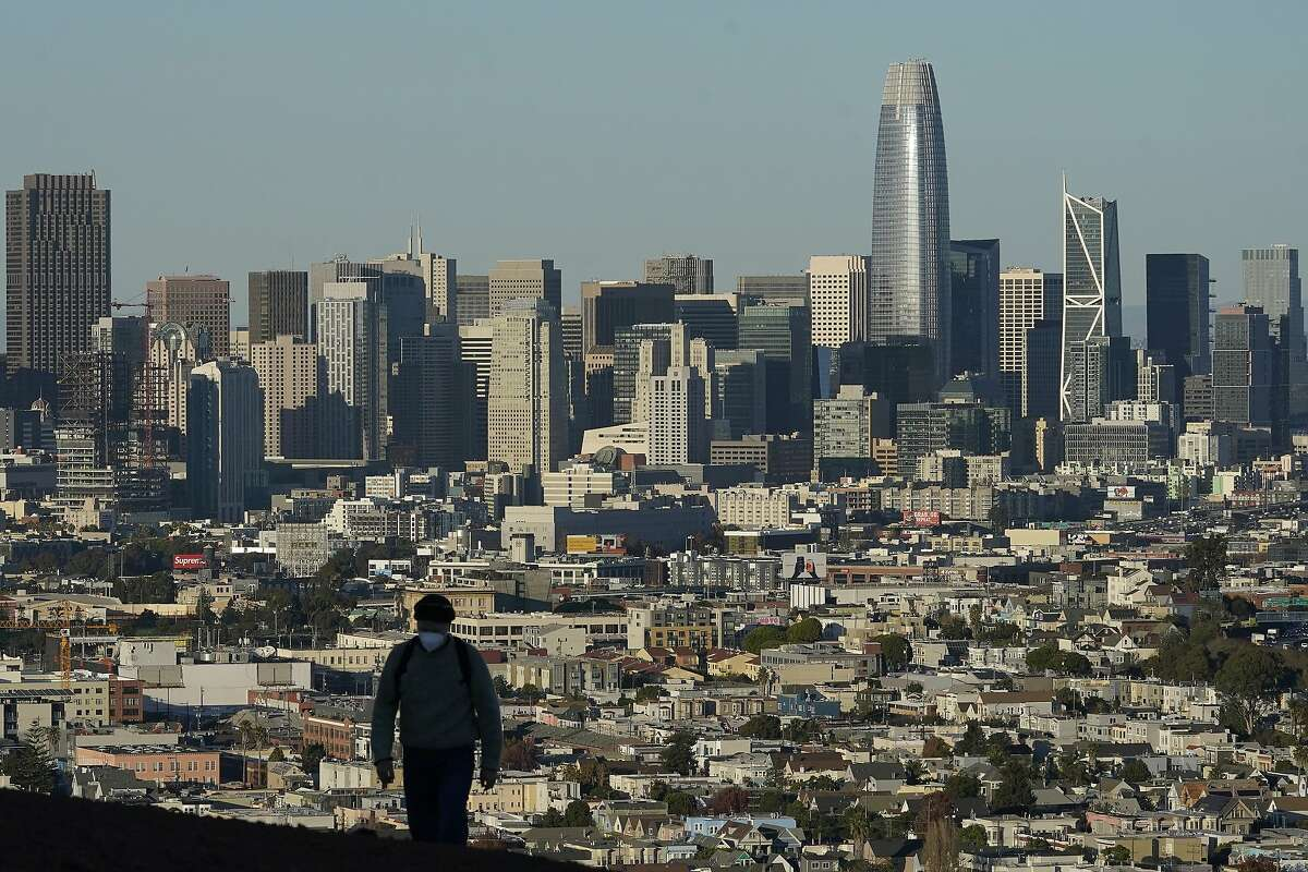 In this Dec. 7, 2020, file photo, a person walks in front of the skyline on Bernal Heights Hill in San Francisco. (AP Photo/Jeff Chiu, File)