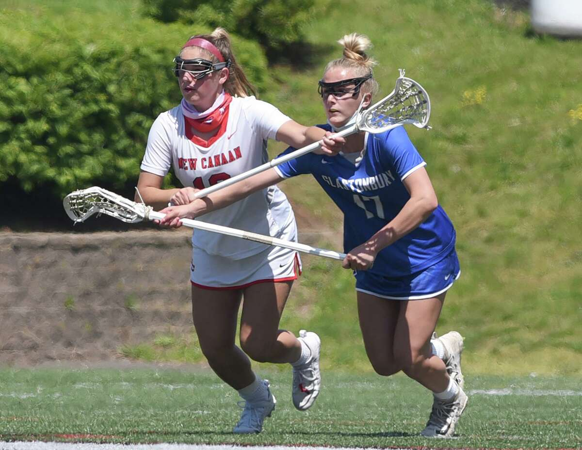 New Canaan's McKenna Harden (13) and Glastonbury's Sam Forrest (17) battles for position during a girls lacrosse game at Dunning Field on Saturday, May 15, 2021. The two will play for North Carolina next year.